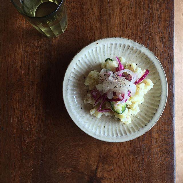 ポテトサラダに紫キャベツと新タマネギのマリネをのせて黒胡椒ひく。白ワインだな。